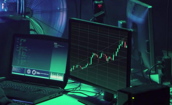 Two monitors demonstrating crypto arbitrage statistics diagrams