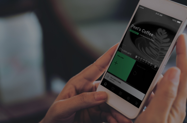 person holding smartphone with procoffee app running on it
