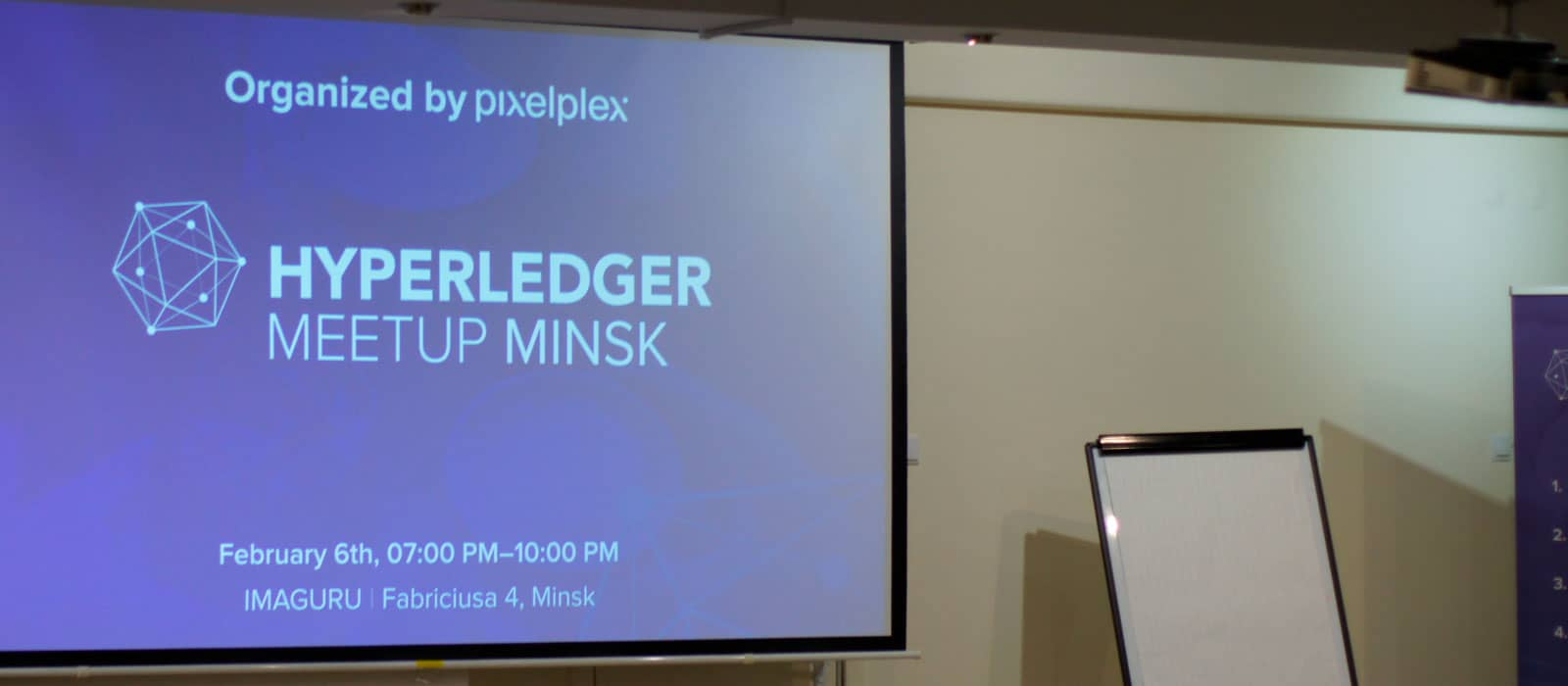 A screen with information about Hyperledger Meetup Minsk 2020 next to a blackboard